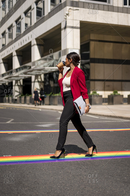 Businesswoman drinking coffee to go while crossing the street on LGBT stripes- London- UK
