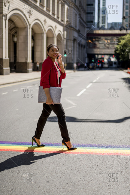 Portrait of businesswoman on the phone crossing the street on LGBT stripes- London- UK
