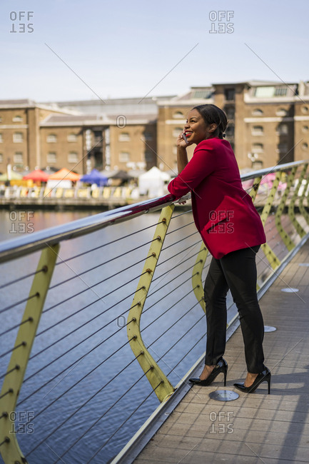 Smiling businesswoman on the phone standing on bridge looking up- London- UK