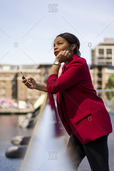 Portrait of pensive businesswoman leaning on bridge railing looking up- London- UK