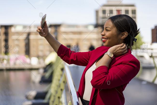 Smiling businesswoman standing on bridge taking selfie with smartphone- London- UK