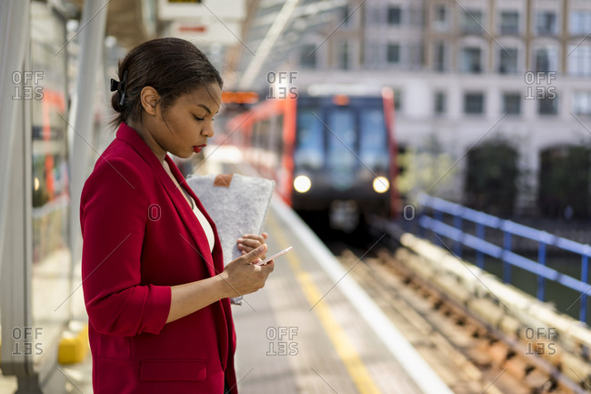Businesswoman standing on platform looking at mobile phone- London- UK