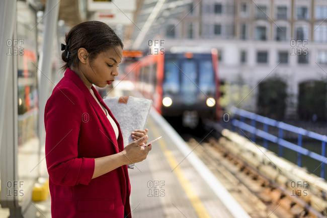 Businesswoman standing on platform looking at mobile phone- London- UK