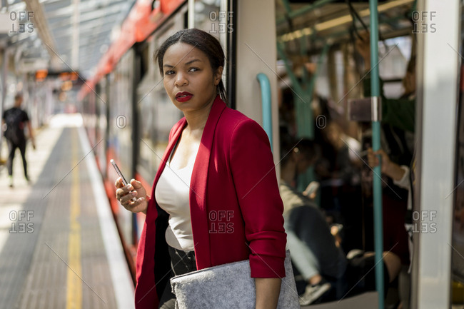 Portrait of businesswoman with cell phone getting out off the train- London- UK