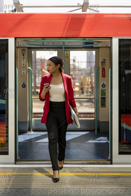 Businesswoman with cell phone getting out off the train- London- UK