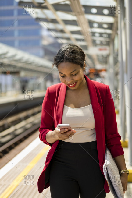 Smiling businesswoman on platform looking at mobile phone- London- UK
