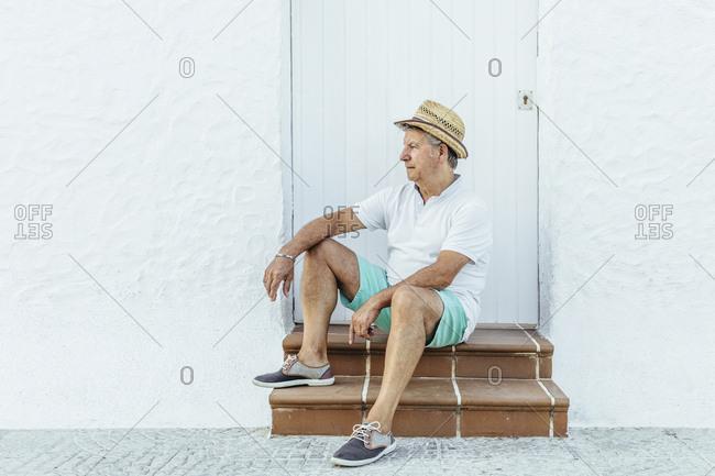 Senior tourist sitting on stoop in a village- El Roc de Sant Gaieta- Spain