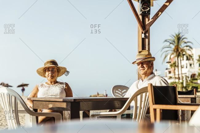 Senior couple sitting at a bar terrace at the beach- El Roc de Sant Gaieta- Spain