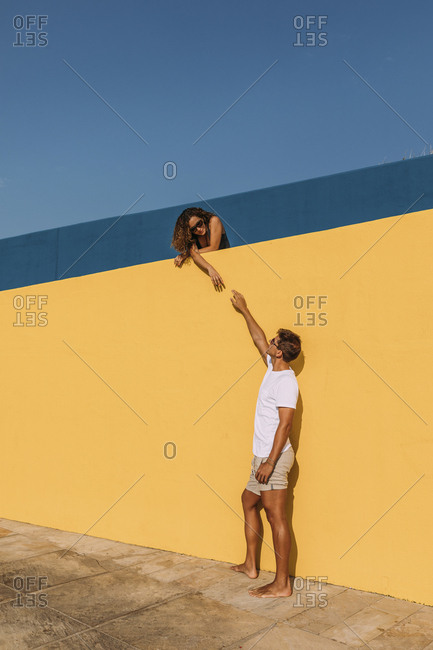Young man reaching out for woman behind a yellow wall