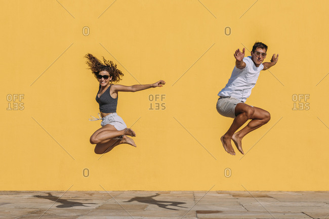 Young couple jumping in front of a yellow wall