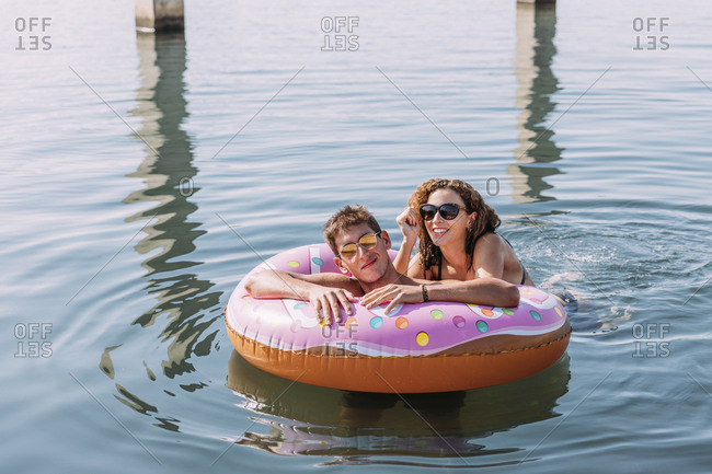 Young couple bathing in the sea on inflatable float in donut shape