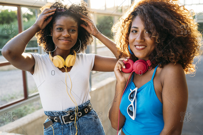 Portrait of two happy young women  with headphones at evening twilight