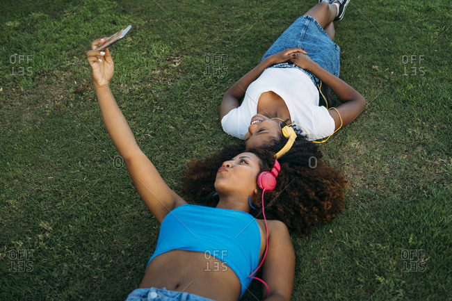 Two young women with headphones lying on a meadow taking selfie with smartphone