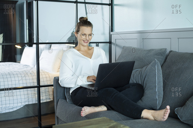 Woman working in hotel room- sitting on couch