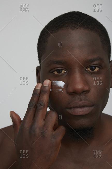 Portrait of African man applying face cream