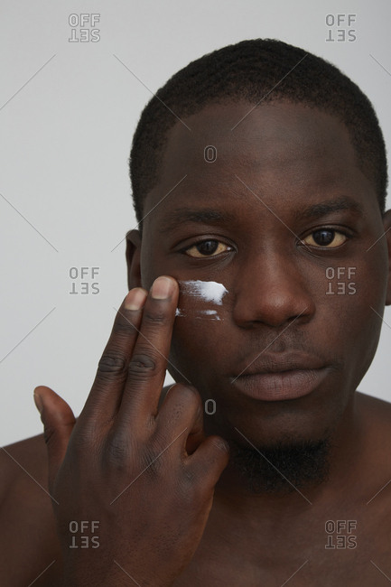 Portrait of African man applying face cream