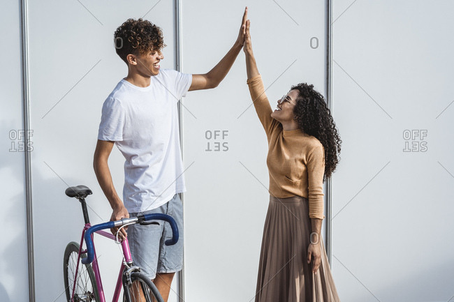 Happy couple with bicycle standing in front of white fence- high-fiving