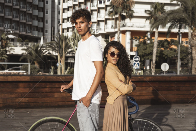 Cool couple with bicycle in the city- standing back to back