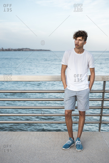 Young man standing on bridge by the sea- with hands in pockets