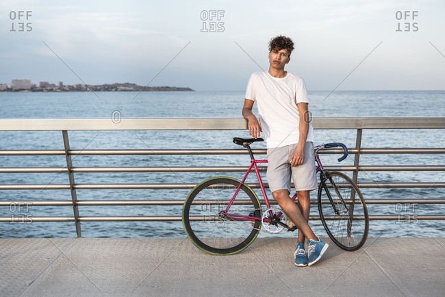 Young man with bicycle-  standing on bridge by the sea