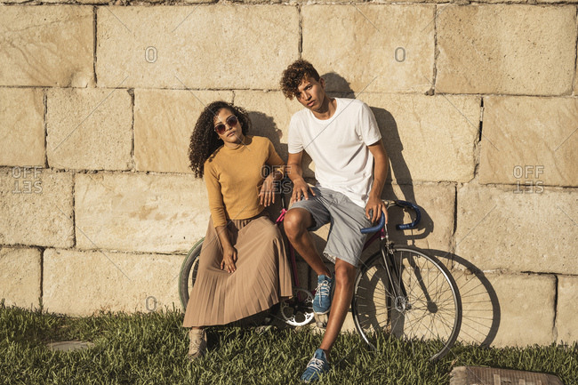 Young couple with bicycle- leaning on stone wall- looking cool