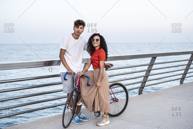 Young couple with bicycle- standing on bridge by the sea