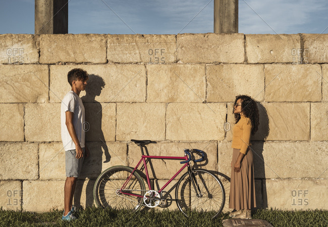 Young couple with bicycle- standing in front of wall- face to face