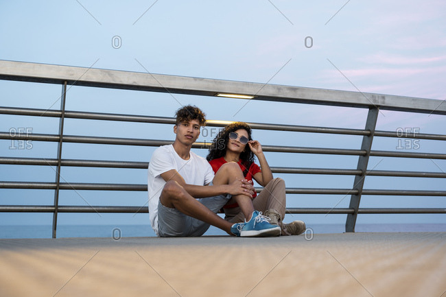 Young couple sitting on bridge by the sea