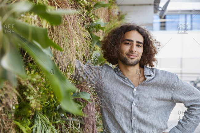 Portrait of young man in front of plant wall