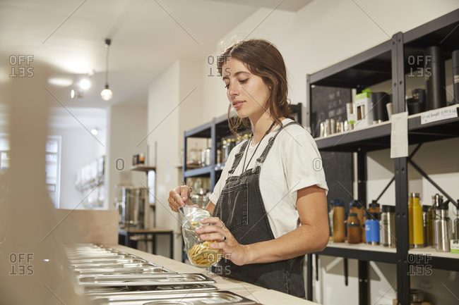 Young woman in packaging-free supermarket filling pasta into jar