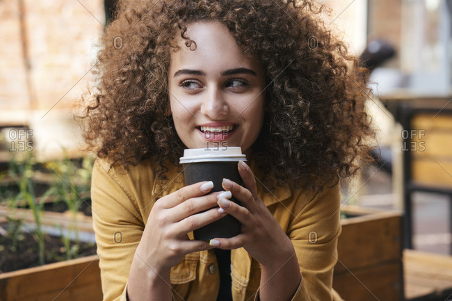 Portrait of smiling teenage girl drinking coffee to go outdoors
