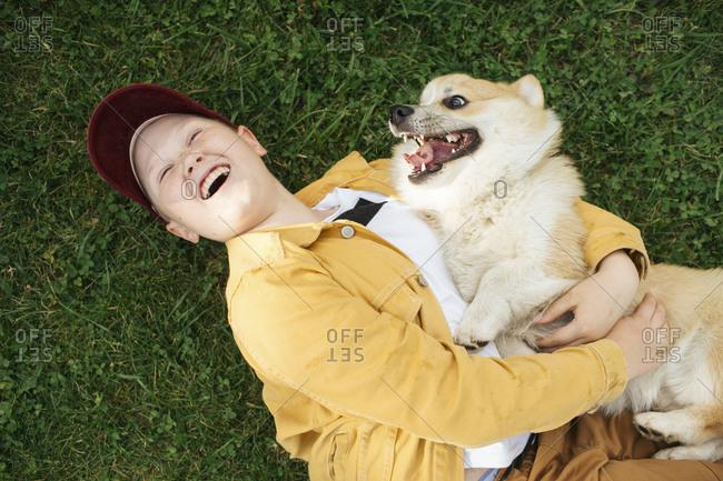 Boy with Welsh Corgi Pembroke lying on meadow