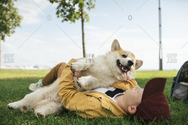 Boy with Welsh Corgi Pembroke in a park