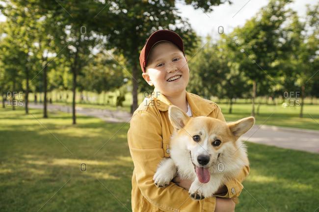Smiling boy holding his Welsh Corgi Pembroke in a park