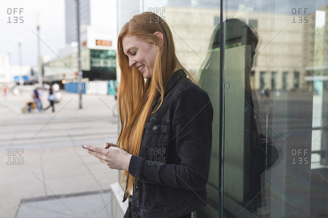 Redheaded young woman text messaging- Berlin- Germany