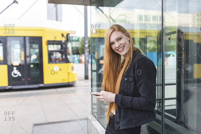 Portrait of redheaded young woman with smartphone in the city- Berlin- Germany