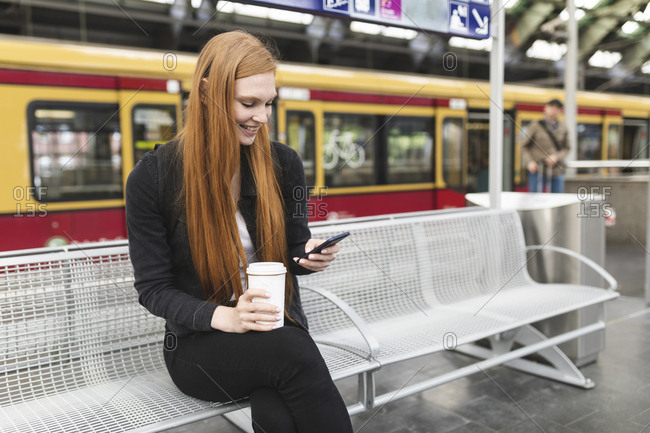 Redheaded young woman with coffee to go waiting at platform using smartphone- Berlin- Germany