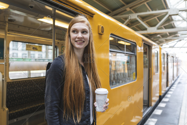 Portrait of redheaded young woman with coffee to go getting out of train- Berlin- Germany