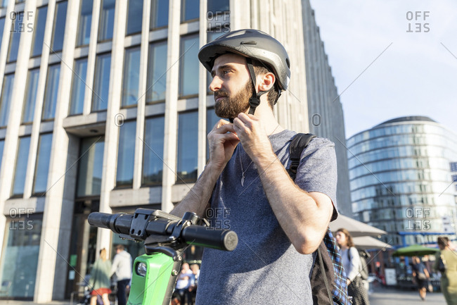 Man using e-scooter in Berlin- fastening safety helmet- Germany