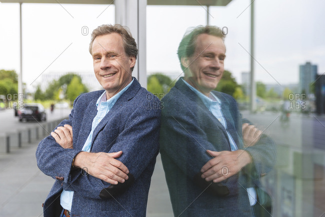 Portrait of confident senior businessman standing at glass front