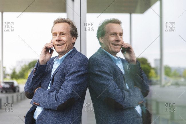 Portrait of smiling senior businessman on the phone at  glass front