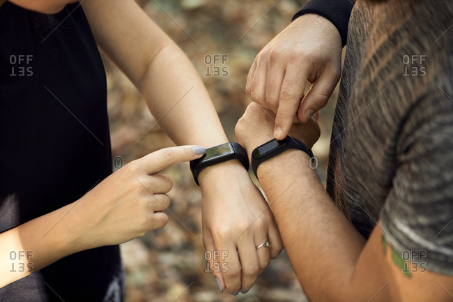 Close-up of sporty couple checking smartwatches
