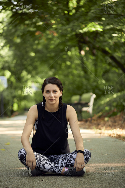 Portrait of sporty young woman sitting on forest path