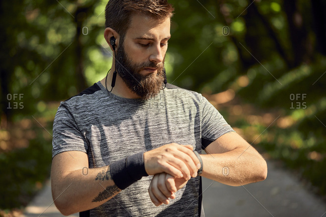 Portrait of sporty man with earphones in forest checking his smartwatch