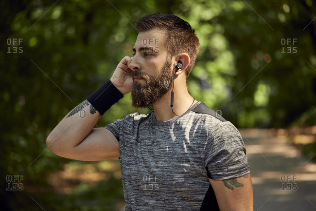 Portrait of sporty man with earphones in forest