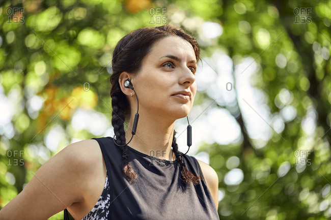Portrait of sporty young woman with earphones in forest