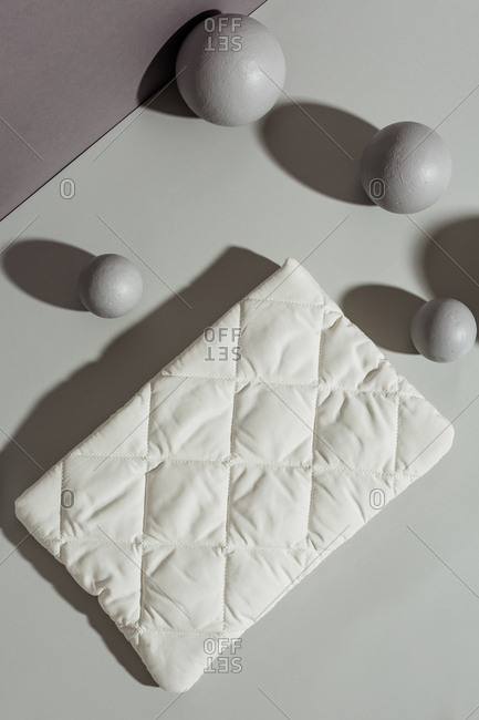 Overhead view of a quilted white pocketbook against grey rectangles and spheres