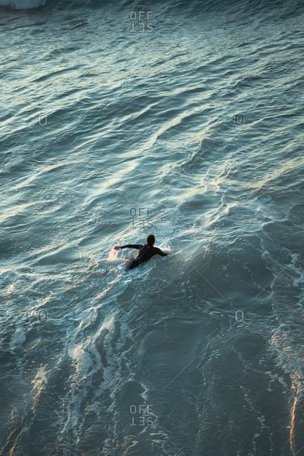 Surfer paddling on the beautiful water of Zurriola Beach in San Sebastian