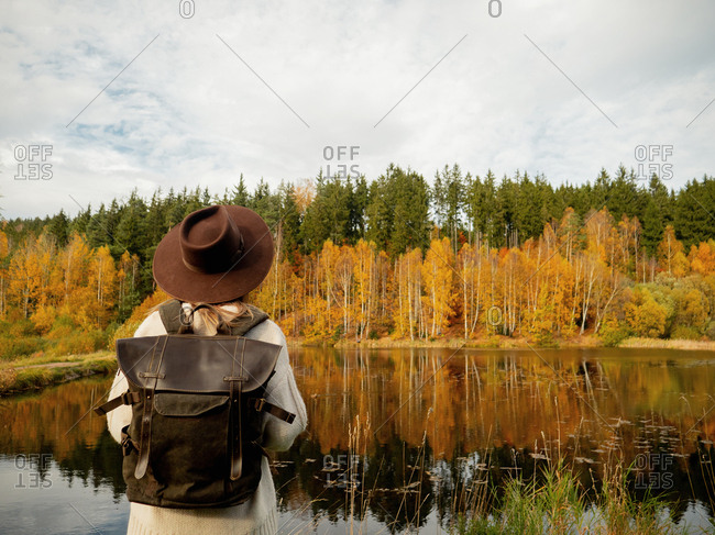 Woman with backpack stay near lake in autumn season time