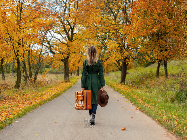 Woman in green cloak with suitcase on countryside road in autumn season time
